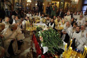 Патриарх Кирилл стоит на коленях перед гробом убиенного свящ. Даниила Сысоева
